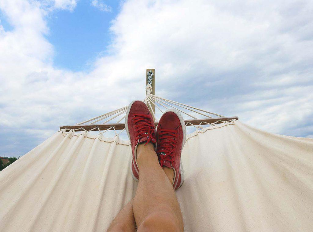 Person liegt auf einer Hängematte und hat rote Schuhe an