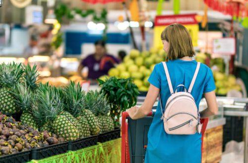 Frau, Die Neben Einkaufsregalen Steht Und Besser Sparen