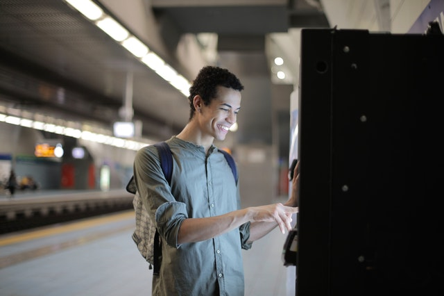 Ein junger Mann steht am Geldautomat