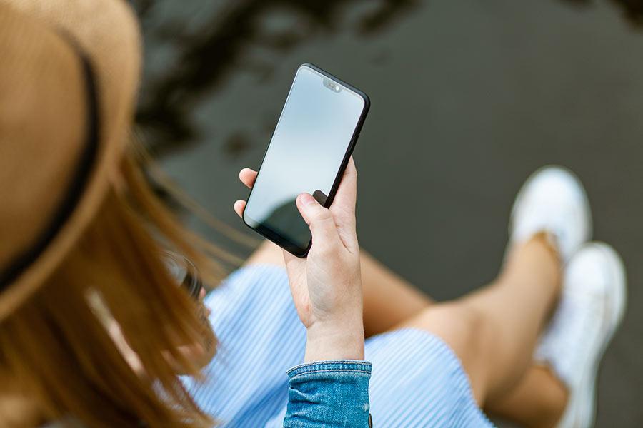 Frau schaut auf ihr Handy, ihr Handyvertrag ist zu teuer