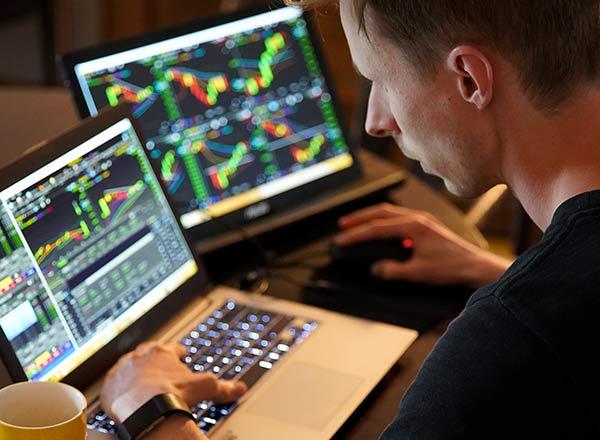 Daytrading Erklärt. Mann Sitzt Vor Einem Laptop, Auf Dem Börsenkurse Angezeigt Werden. Er Ist Trader.